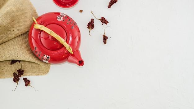 Rode oosterse traditionele theepot met kruiden die op witte achtergrond wordt geïsoleerd