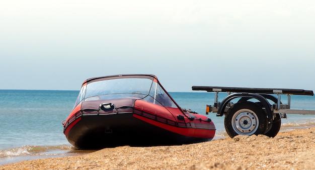 Rode opblaasbare boot en boottrailer aan de kust.