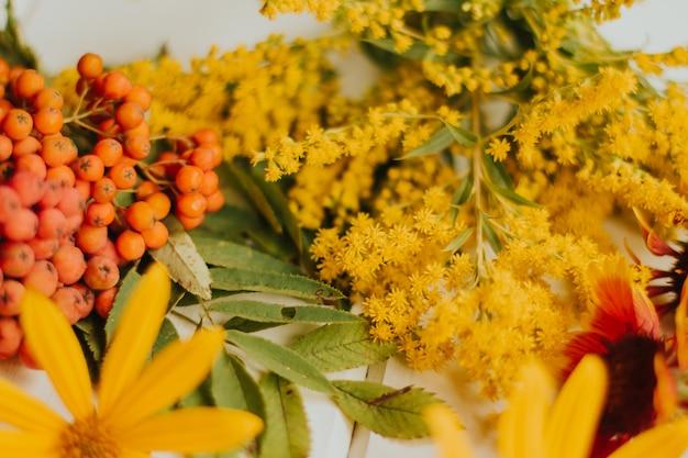 Rode, oranje en gele herfstbloemen. herfst droog esdoornblad. rode lijsterbessen.