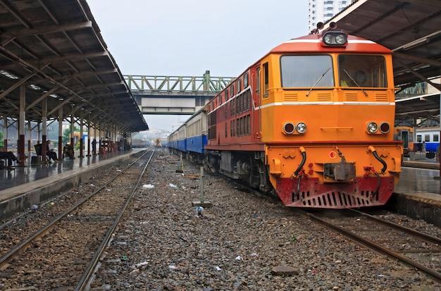 Rode oranje trein, diesel locomotief, op het station van bangkok van het platform thailand