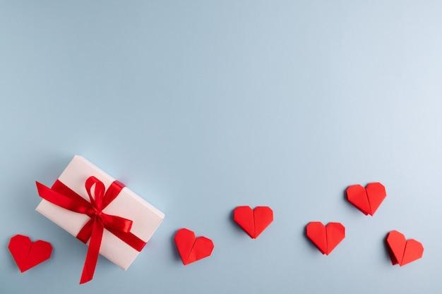 Rode origami harten en presenteren op een pastel blauwe tafel.
