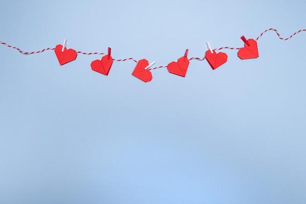 Rode origami harten op touw met wasknijpers, op een pastel blauwe tafel.