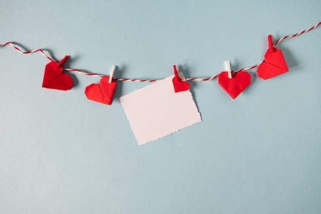 Rode origami harten op touw met wasknijpers
