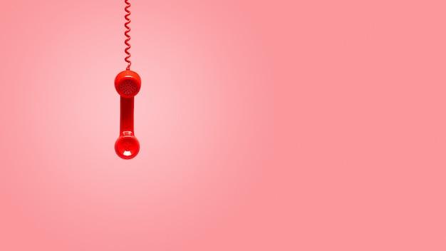 Rode oude telefoonhoorn die op roze achtergrond hangen