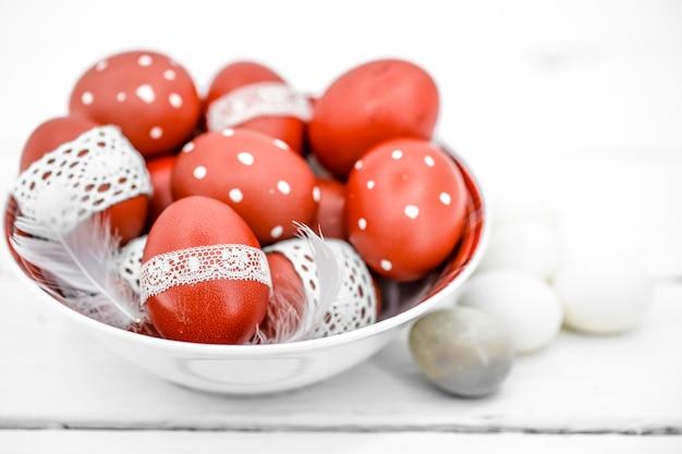 Rode paaseieren op een witte plaat en op wit gebonden kantband, close-up