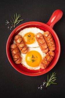 Rode pan met gebakken eieren en worstjes op een zwarte ondergrond.