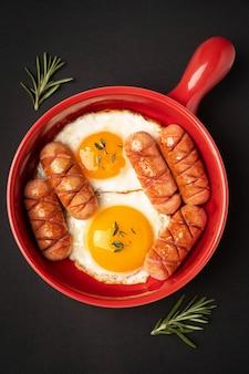 Rode pan met gebakken eieren en worstjes op zwart