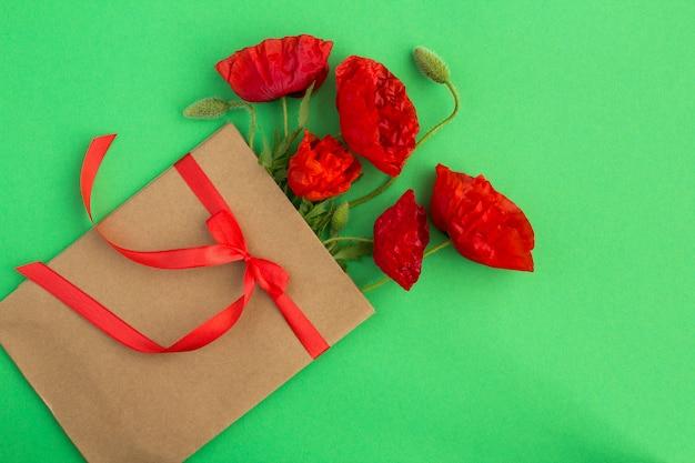 Rode papavers in een envelop gebonden met een lint
