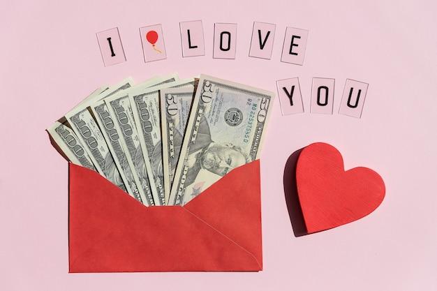Rode papieren envelop met dollarbiljetten en rood hart geïsoleerd op roze achtergrond