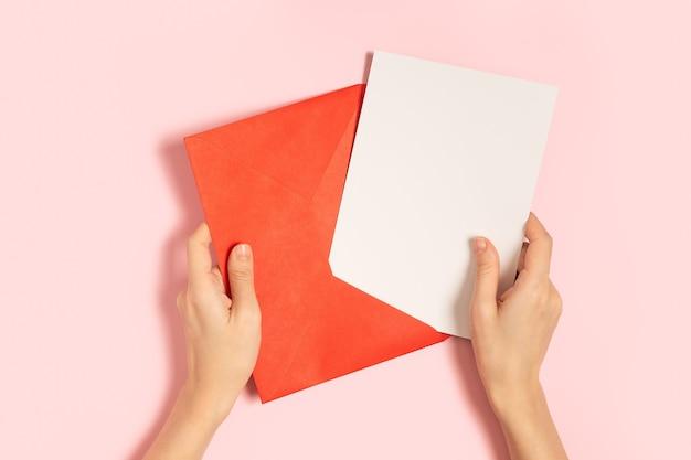 Rode papieren envelop met lege witte notitie mockup in handen van de vrouw, binnen op roze pastel achtergrond