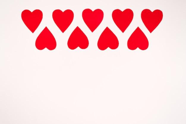 Rode papieren harten op witte achtergrond, rand, kopie ruimte. valentijnsdag kerstkaart