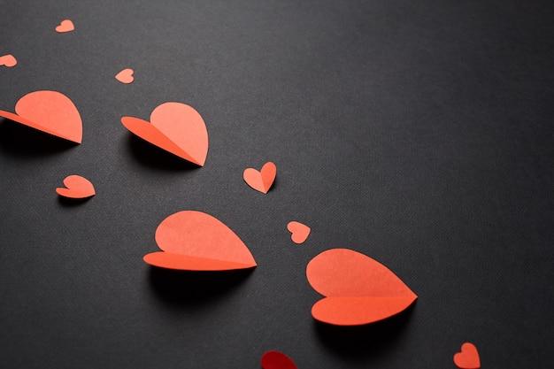 Rode papieren harten op zwarte achtergrond