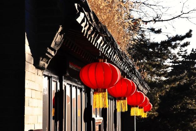 Rode papieren lantaarns die op het dak van chinese huizen hangen.