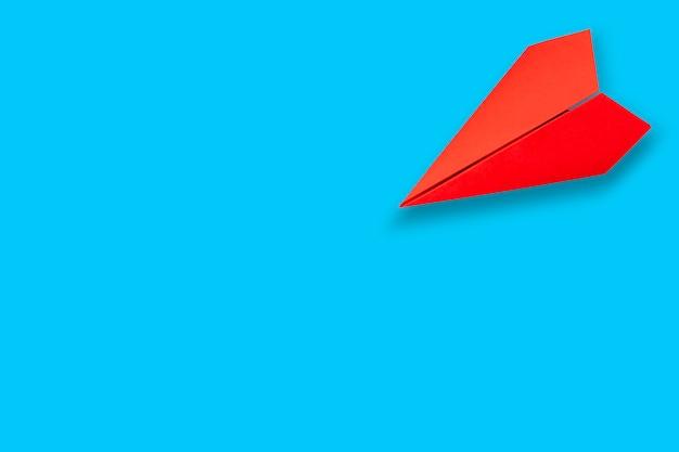 Rode papieren vliegtuig op blauw