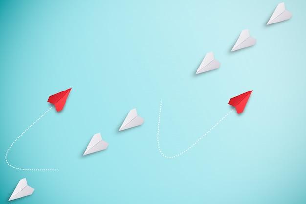 Rode papieren vliegtuig uit lijn met wit papier om te veranderen verstoren en nieuwe normale manier vinden op blauwe muur. lift en zakelijke creativiteit nieuw idee om innovatietechnologie te ontdekken.