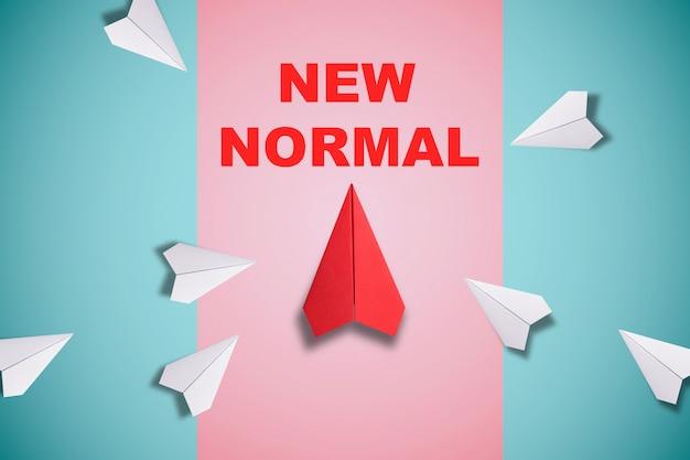 Rode papieren vliegtuig uit lijn met wit papier te veranderen verstoren en het vinden van nieuwe normale manier op blauwe achtergrond. lift en zakelijke creativiteit nieuw idee om innovatietechnologie te ontdekken.