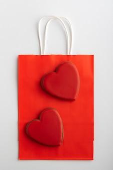 Rode papieren zak en peperkoek hartjes op witte achtergrond. verticaal frame. moederdag. valentijnsdag.