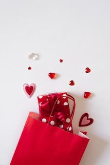 Rode papieren zak, geschenkdoos met een strik en verschillende harten