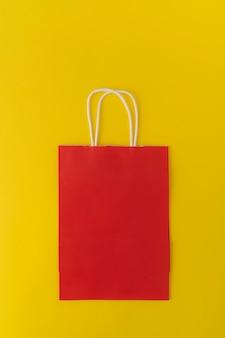 Rode papieren zak op gele achtergrond. plastic tas. kopieer ruimte. bespotten. verticaal frame.