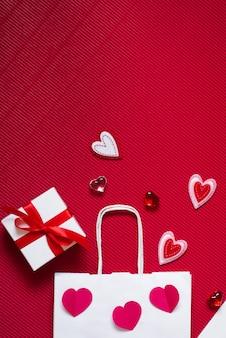 Rode papieren zak, witte geschenkdoos met rood satijnen lint en verschillende harten op rood