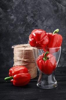 Rode paprika in een vaas op een donkere achtergrond. verse groenten en voedselconcept