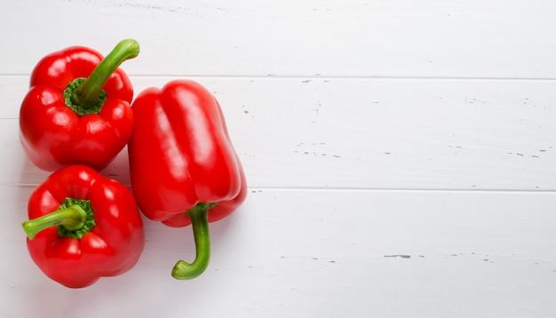 Rode paprika op een witte houten achtergrond