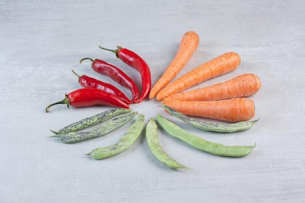 Rode paprika's, groene bonen en wortelen op stenen achtergrond. hoge kwaliteit foto