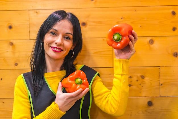 Rode paprika's in de hand van een donkerbruin kaukasisch fruitmeisje, werkzaam in een groenteboer