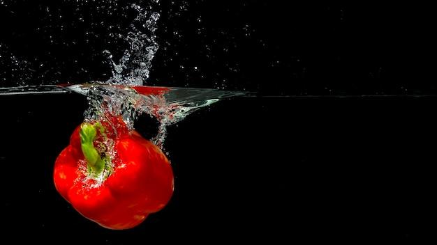 Rode paprika spatten in water over zwarte achtergrond