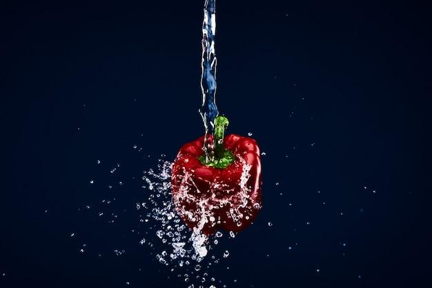 Rode paprikapeper die onder water wordt gewassen.