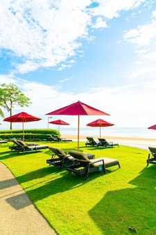 Rode paraplu en strandstoel met overzeese strandachtergrond en blauwe hemel en zonlicht