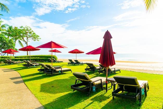 Rode paraplu en strandstoel met zee strand en blauwe lucht en zonlicht