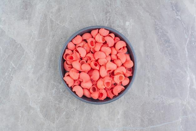 Rode pasta's in een zwart metallic kopje op het marmer