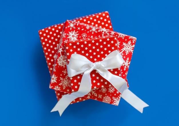 Rode patroon kerstcadeau dozen geïsoleerd op blauw bovenaanzicht