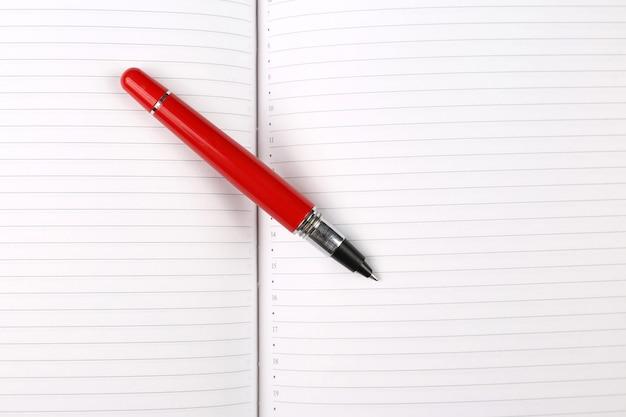 Rode pen die op een open notitieboekje ligt