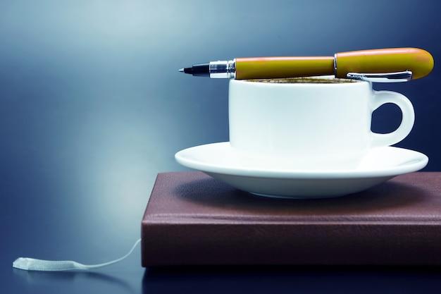Rode pen op een witte kop zwarte koffie. kantoorartikelen