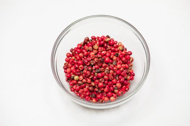 Rode peperkorrels in glazen kom geïsoleerd op een witte achtergrond, biologische hete kruiden, gedroogde peperkorrels ballen, indiase natuurlijke kruiden. food concept, chili peper korrels cosmetische ingrediënten. tekstruimte
