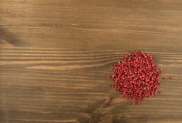 Rode peperkorrels op houten achtergrond