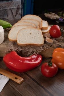 Rode pepers en brood op een houten tafel