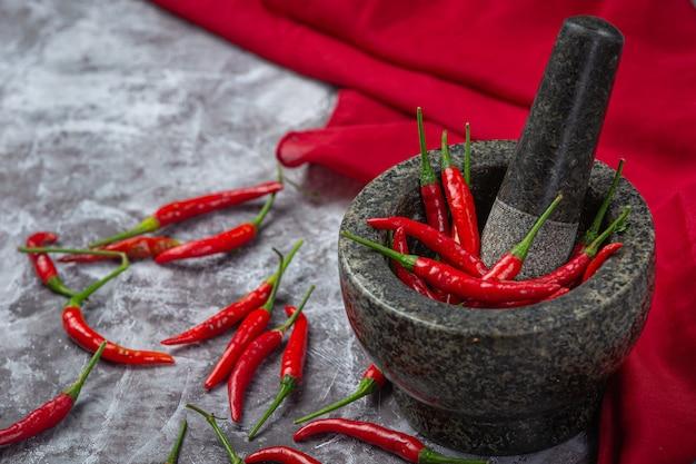 Rode pepers zijn in een stenen vijzel op een zwarte ondergrond.