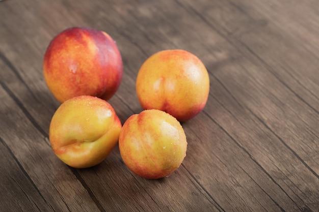 Rode perziken geïsoleerd op een houten bord.