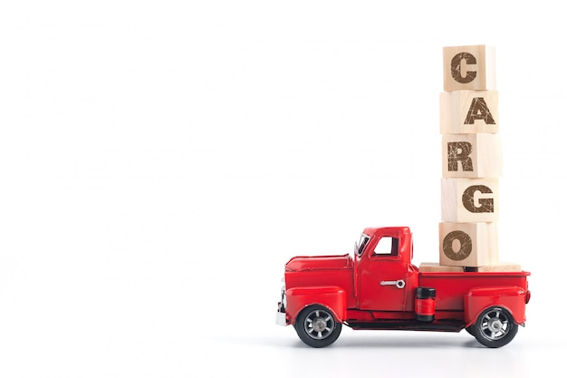 Rode pick-up draagt hout blok met tekst cargo