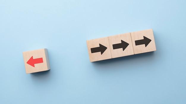 Rode pijl afdrukscherm op houten blok verandert van richting van rechts naar links die verschillen van zwarte pijlen