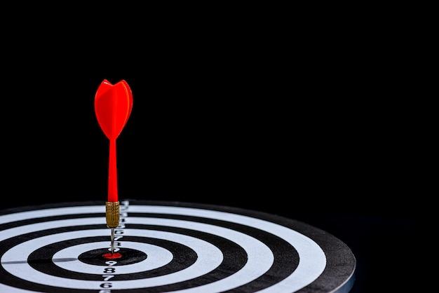 Rode pijl die in het midden van het doel raakt, is dartbord op zwart