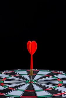 Rode pijl die in het midden van het doel raakt, is een dartbord op zwarte achtergrond