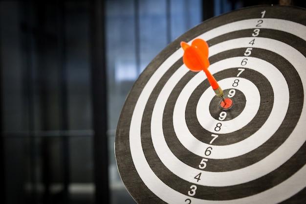 Rode pijlpijl die in het doelcentrum van dartboard op bullseye met zonlicht uitstekende stijl raakt