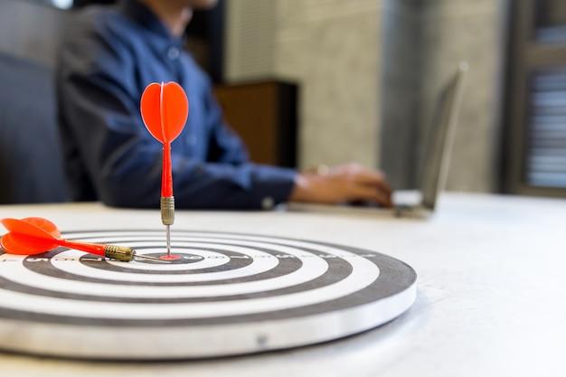 Rode pijltjepijl die in het doelcentrum raken van dartboard op bullseye, het concept van het bedrijfs de groeisucces.