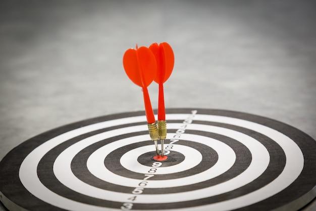 Rode pijltjepijl die in het doelcentrum van dartboard op bullseye met zonlicht uitstekende stijl raken