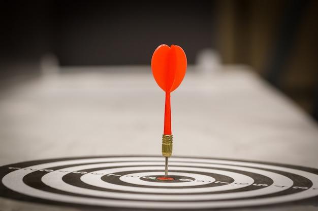 Rode pijltjepijl die in het doelcentrum van dartboard op bullseye raakt