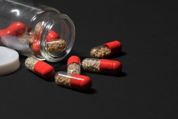 Rode pillen met witte korrels vielen uit een glazen pot op een donkere achtergrond medicinale capsules